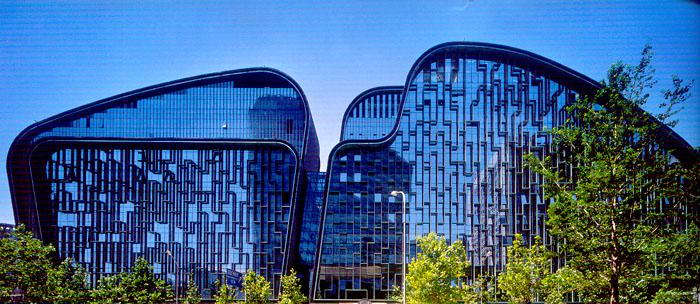 """北京数字出版信息中心 Beijing Digital Press Information Center 位于朝阳门内的这座建筑受控于一条复杂的高度控制线,从南到北30米到40多米再到20多米,导致建筑轮廓落差很大,并分别为南北两期。与南北向的高度变化相比,用地东西向的尺度反差也很大,西侧保留着一套清朝府邸""""五爷府"""",东侧与庞大的中海油总部大楼隔街相对。需要找到满足上述条件,且不失建筑完整性的方法。 设计尝试用曲面连接各高度的控制点,不仅满足日照的条件,也争取了尽可能多的可利用空间。"""